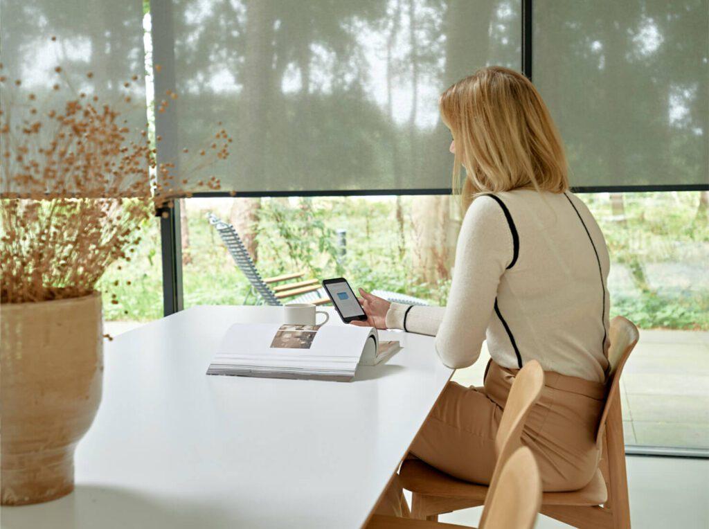 vrouw die bij het raam zit en deslimme screens bedient via een app